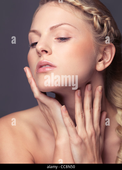 Beauty portrait of a young woman touching soft skin on her face and neck - Stock Image