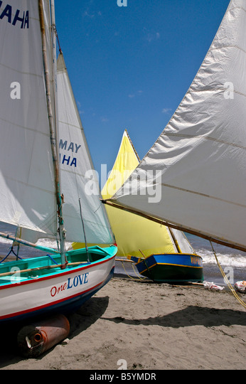 Grenada beach at Gouyave racing sailboats sails bright colors red white yellow blue southern caribbean - Stock Image