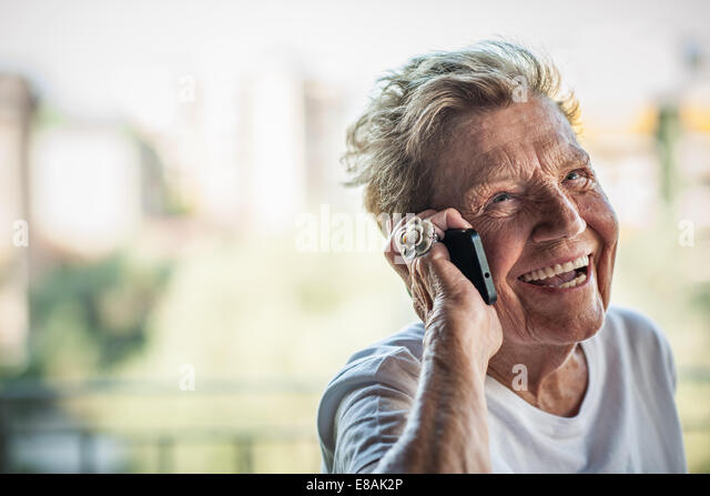 A very senior woman chatting and laughing on smartphone on apartment balcony - Stock Image