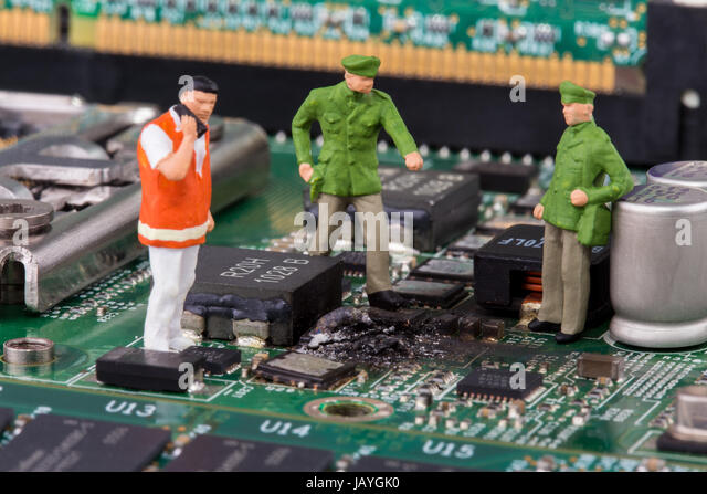 miniature police on a computer mainboard - studio shot - Stock Image