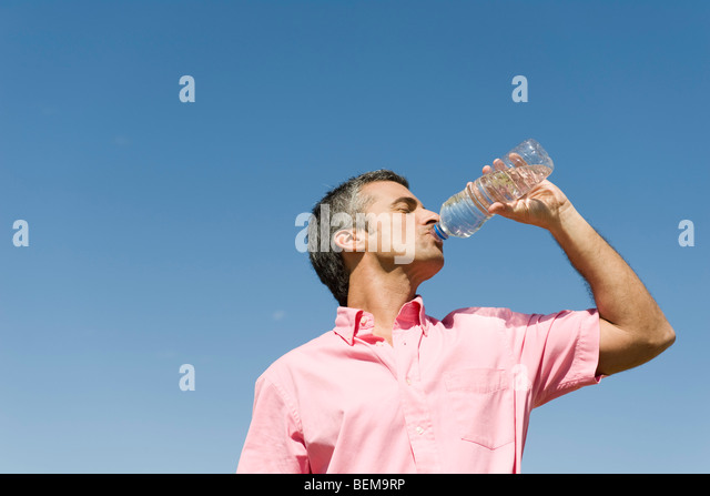 Man standing outdoors drinking from bottle of water, low angle view, blue sky in background - Stock Image