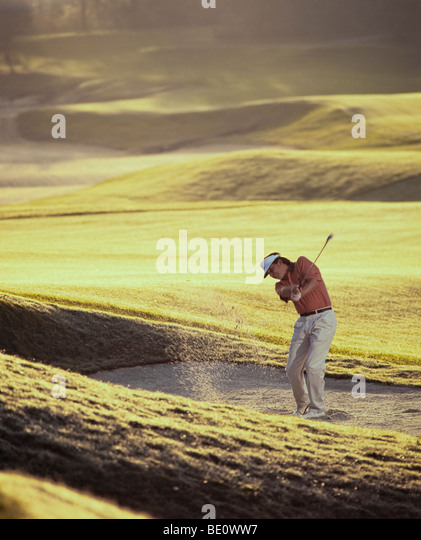 Man golfer chipping from sand trap - Stock Image