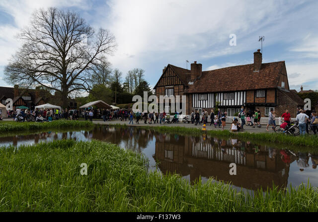 People visit a busy local village fete around a pond in front of a timbered building in Ashridge, England - Stock Image