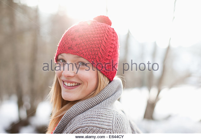 Close up portrait of smiling woman with red knit hat - Stock Image