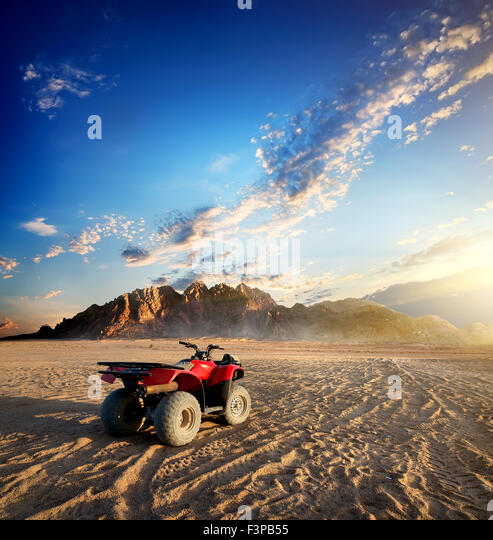 Quad bike in sand desert near mountain - Stock Image