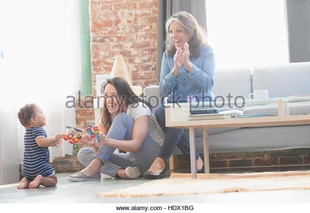 Hispanic mother and grandmother playing with baby boy - Stock Image