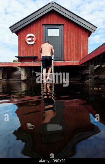 Man climbing swim ladder - Stock Image