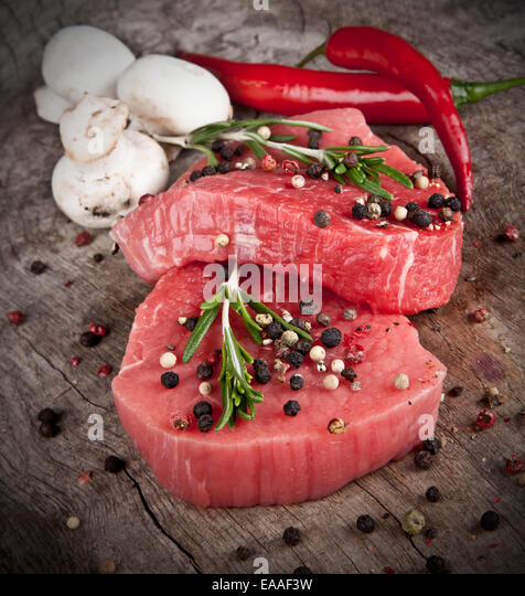 Raw beef steaks prepared for grill - Stock Image
