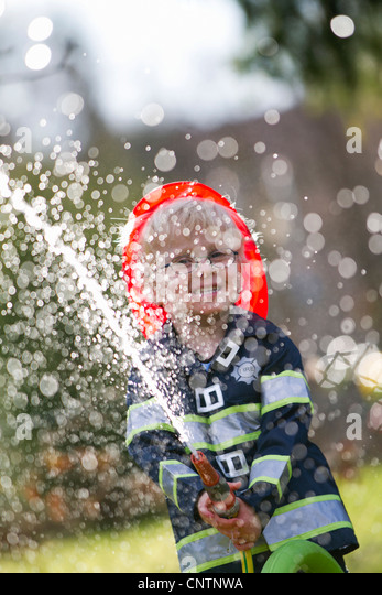 Boy in fireman costume playing with hose - Stock Image
