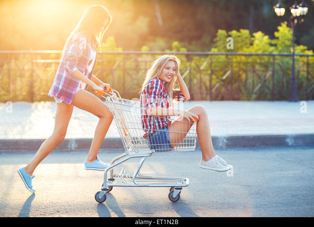 Two happy beautiful teen girls driving shopping cart outdoors, lifestyle concept - Stock Image
