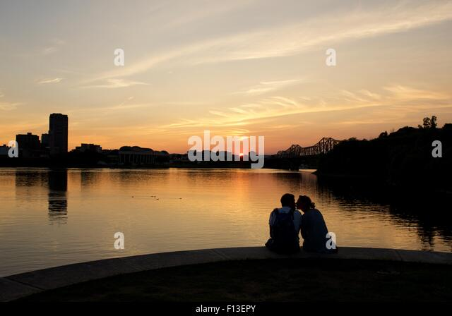 Silhouette of couple sitting by a river kissing, Ottawa, Ontario, Canada - Stock Image