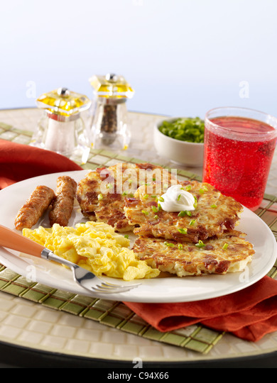 Potato pancakes served with eggs, sausage and cranberry juice - Stock Image