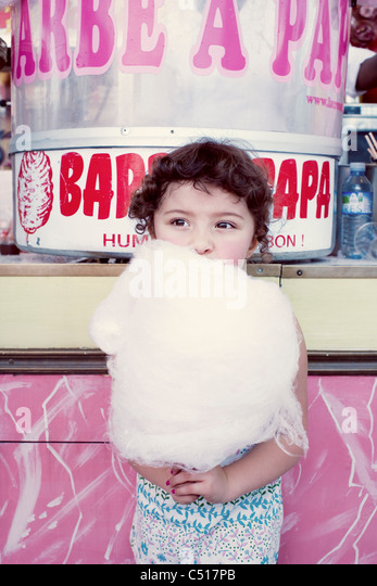 Little girl eating cotton candy at fair - Stock Image