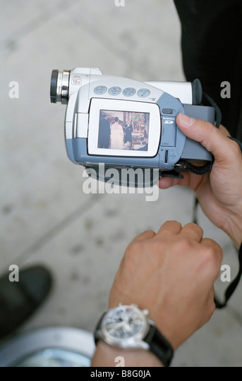 Man with a Digital Camera which shows a Picture of a Wedding - Technology - Stock Image