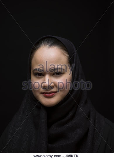 Portrait smiling Middle Eastern woman wearing black hijab against black background - Stock Image