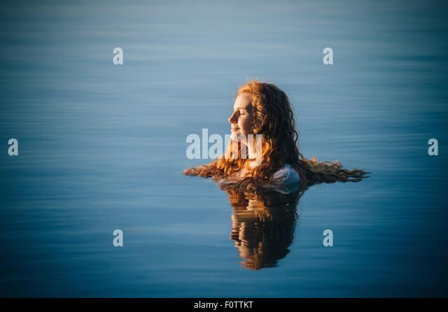Head and shoulders of young woman with long red hair in lake with eyes closed - Stock Image