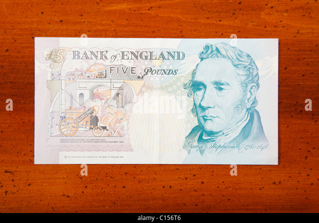 Five pound British currency note on table showing George Stephenson - Stock Image