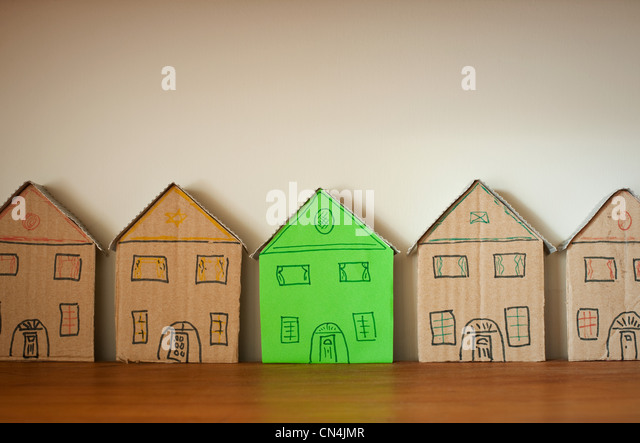 One green cardboard house amongst others - Stock Image