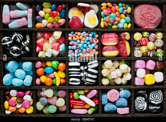Colourful assorted childrens sweets and candy in a wooden tray - Stock Image