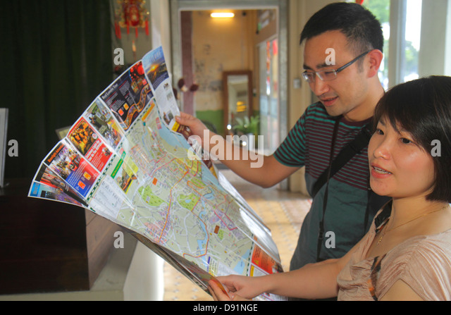 Singapore Jalan Besar Kam Leng Hotel lobby Asian man woman couple looking at map inside interior - Stock Image