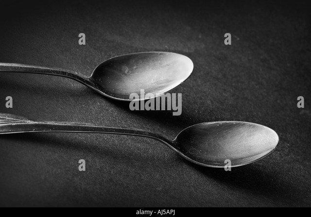 Two oxidized spoons resting on a table. - Stock Image