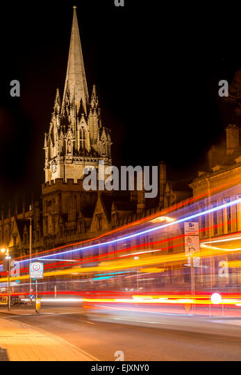 The University Church of St Mary, Oxford, UK from the High Street as traffic passing by leaves light trails - Stock Image