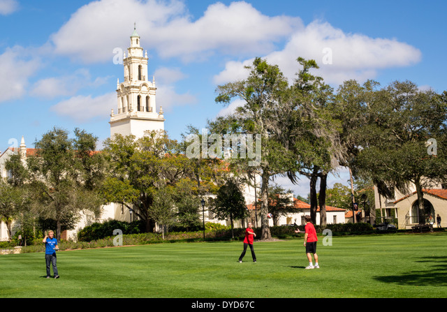 Winter Park Florida Rollins College campus school Knowles Memorial Chapel lawn student throwing ball teen boy girl - Stock Image