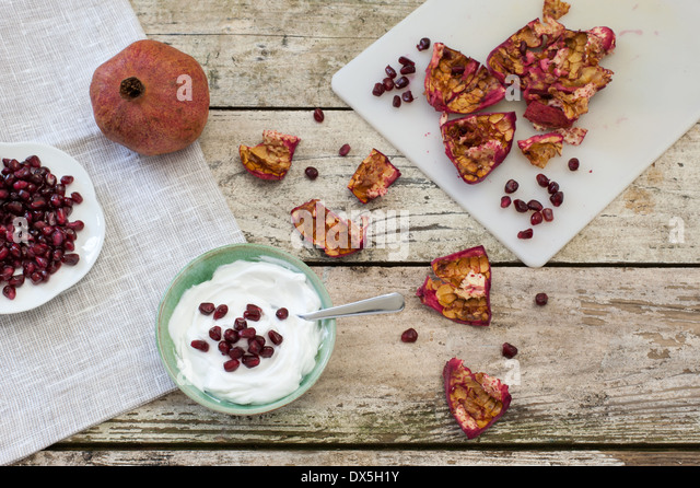 Healthy snack a bowl of yogurt and pomegranate seeds. A whole fruit, seeds and skin on a chopping board, on a rustic - Stock Image