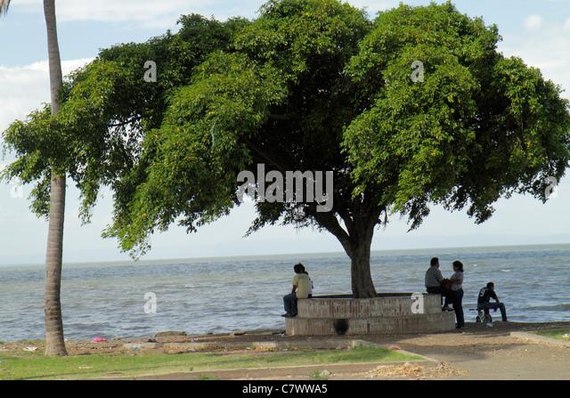 Managua Nicaragua El Malecon Lake Managua Xolotlan waterfront recreational area tree canopy shade man woman couple - Stock Image