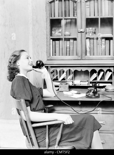 1930s 1940s TEENAGE GIRL SITTING AT DESK TALKING ON OLD BLACK ROTARY DIAL PHONE - Stock Image