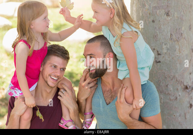Two sisters sitting on fathers shoulders in park - Stock-Bilder