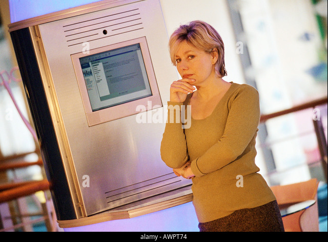Woman standing in front of computer screen, portrait - Stock Image