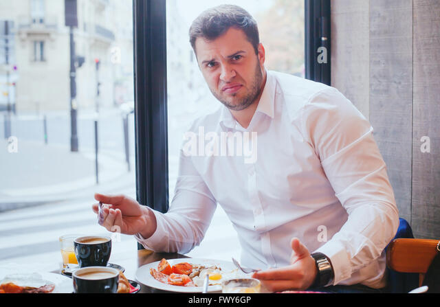 displeased angry customer in restaurant, man unhappy with food and bad service - Stock Image