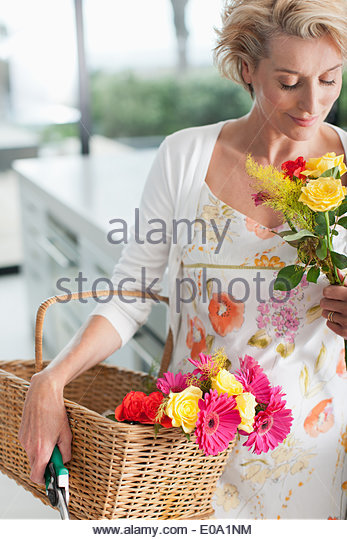 Mature woman with basket of flowers - Stock Image