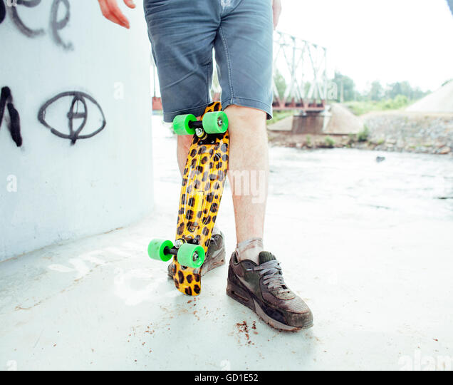 young handsome real hipsrter guy bearded staying under the bridge extreeme with leopard skateboard, lifestyle people - Stock Image