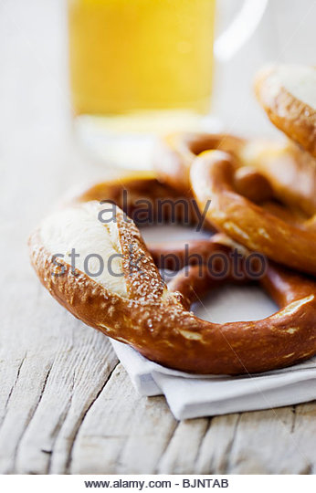 Several soft pretzels and glass of beer - Stock Image
