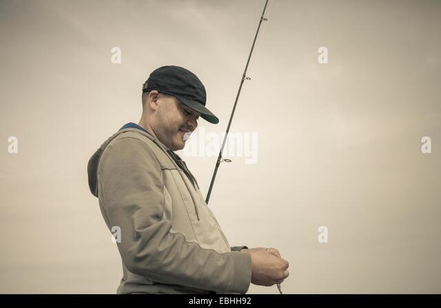 Fisherman preparing fishing rod, Truro, Massachusetts, Cape Cod, USA - Stock Image