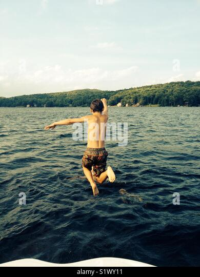 Jumping into a lake - Stock Image
