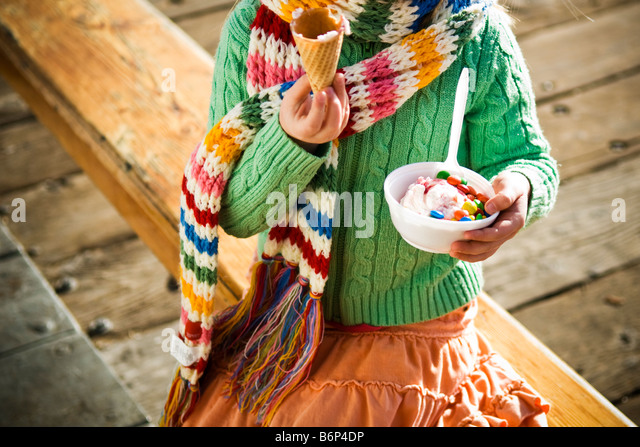 A girl, 4-5 years, enjoys a bowl of ice cream and m&m's on a cold day. - Stock Image
