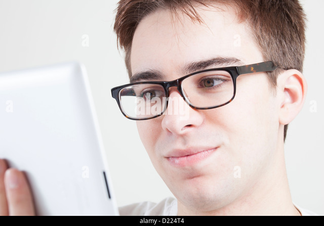Young male wearing glasses looking at the screen of his laptop or digital tablet. Close up. - Stock-Bilder
