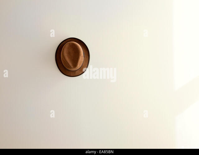 lone brown hat on white wall - Stock Image