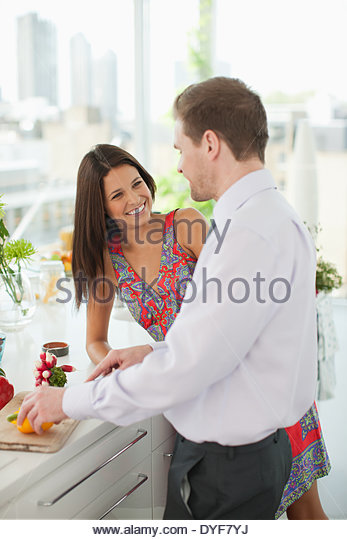 Woman watching husband cutting vegetables in kitchen - Stock Image