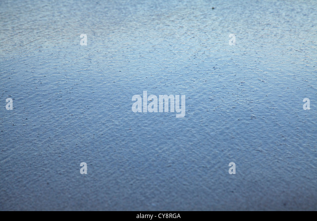 Raindrops hitting surface of water, full frame - Stock Image
