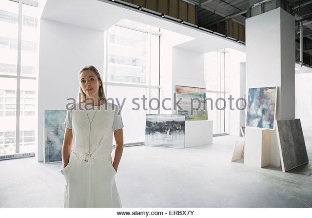 Portrait confident art dealer in art gallery - Stock Image