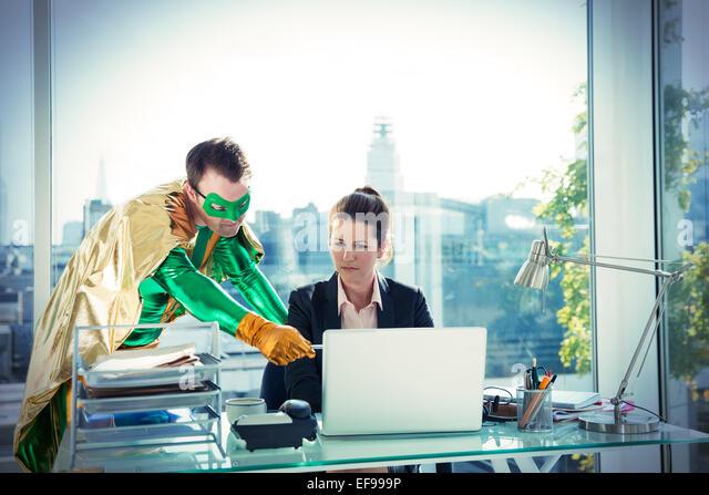Superhero helping businesswoman working at office desk - Stock Image