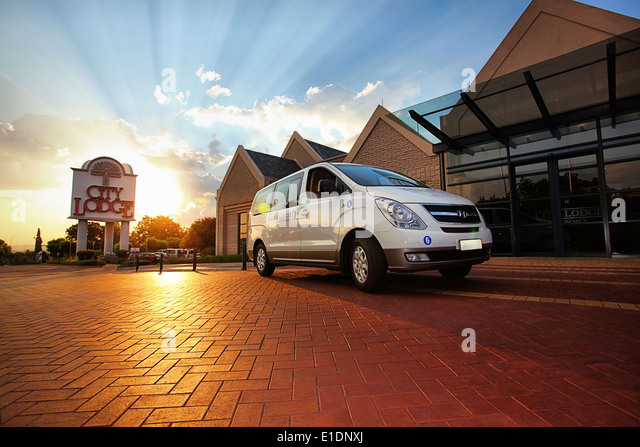 A Hyundai minivan parked outside a City Lodge at sunset - Stock Image