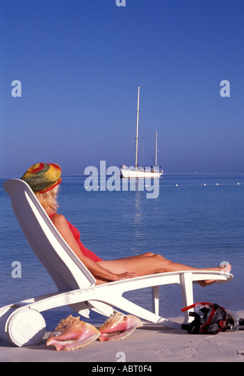JAMAICA Negril Woman in red bathing suit sitting in beach chair with sailboat in background blue sky conchs and - Stock Image