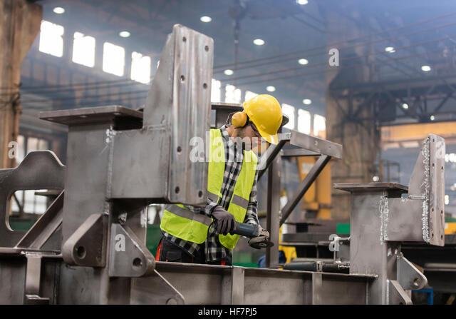 Steel worker working in fabrication factory - Stock Image