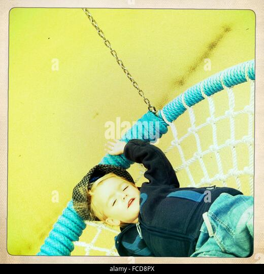 Boy Relaxing On Swing Chair - Stock Image