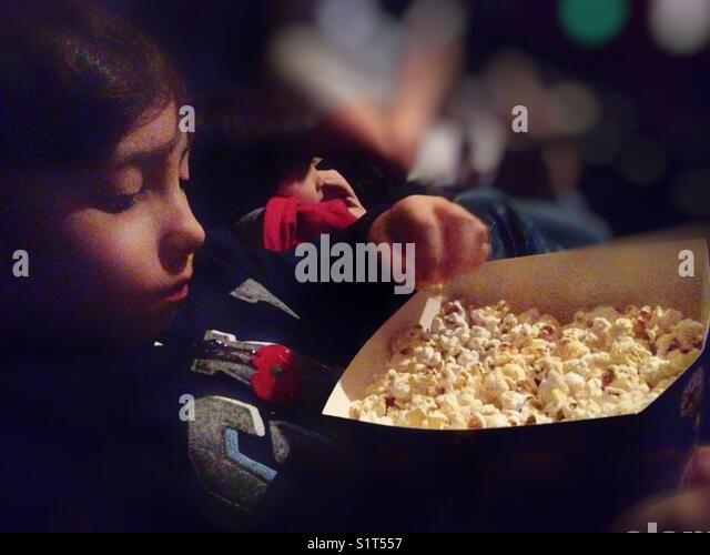 Boy eating popcorn in the cinema. - Stock Image